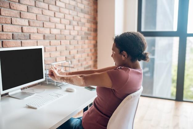Nach einem arbeitsreichen tag. junge afroamerikanerin sitzt am tisch und streckt sich
