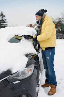 Nach einem großen schneesturm muss das auto vom schnee befreit werden