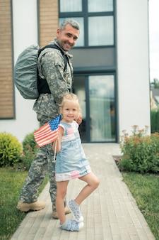 Nach hause gehen. amerikanischer soldat in uniform, der mit seiner tochter nach hause zurückkehrt