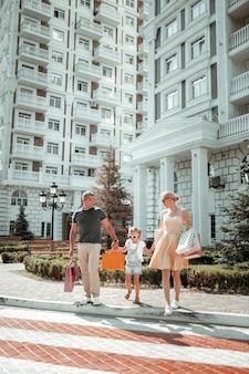 Nach hause gehen. kleine glückliche familie, die händchen hält und auf dem heimweg zusammen die straße überquert.