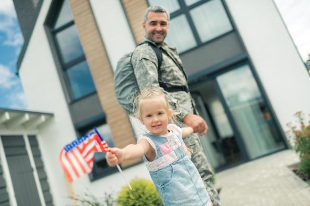 Nach hause kommen. militärmann, der sich extrem glücklich fühlt, während er nach hause kommt und die hand seines schönen mädchens hält