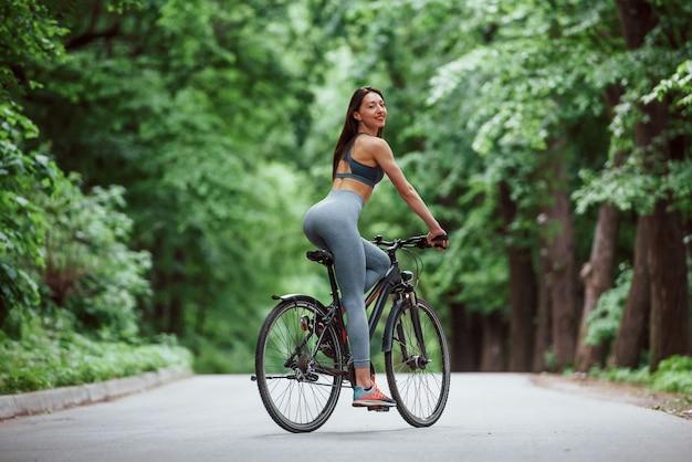 Nach hinten schauen. weiblicher radfahrer auf einem fahrrad auf asphaltstraße im wald am tag