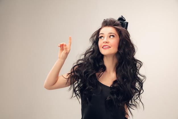 Nach oben zeigend. porträt der schönen jungen frau auf grauer wand. weibliches modell des kaukasischen netten brunette mit dem langen gelockten haar. konzept der schönheit, mode, kosmetik. exemplar