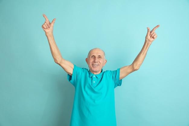 Nach oben zeigend. porträt des kaukasischen älteren mannes lokalisiert auf blauem studiohintergrund. schönes männliches emotionales modell. konzept der menschlichen emotionen, gesichtsausdruck, verkauf, wohlbefinden, anzeige. copyspace.