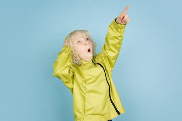Nach oben zeigend. porträt des schönen kaukasischen kleinen jungen lokalisiert auf blauer wand. blondes lockiges männliches modell. konzept des gesichtsausdrucks, menschliche emotionen, kindheit, copyspace.