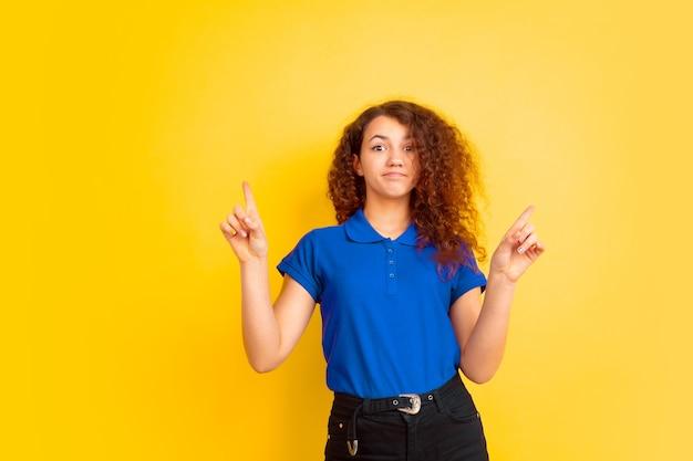 Nach oben zeigend, süß. mädchenporträt des kaukasischen teenagers auf gelbem studiohintergrund. schönes weibliches lockiges modell im hemd. konzept der menschlichen emotionen, gesichtsausdruck, verkauf, werbung, bildung. exemplar.