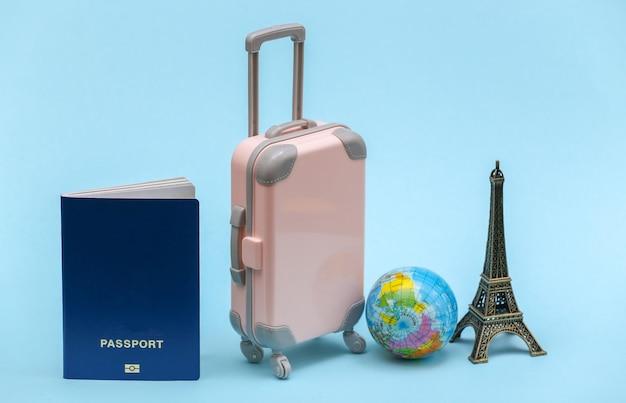 Nach paris gereist. mini-kunststoff-reisekoffer, reisepass, globus und statuette des eiffelturms auf blauem hintergrund.