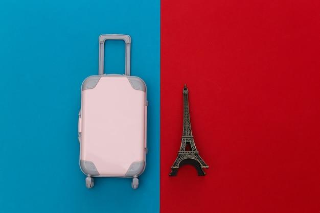 Nach paris gereist. mini-kunststoff-reisekoffer und statuette des eiffelturms auf rot-blauem hintergrund. ansicht von oben. flach legen