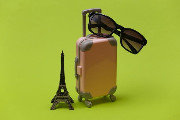 Nach paris gereist. mini reisekoffer aus kunststoff mit sonnenbrille und statuette des eiffelturms auf grünem hintergrund.