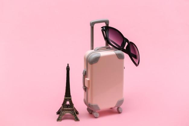 Nach paris gereist. mini-reisekoffer aus kunststoff mit sonnenbrille und statuette des eiffelturms auf rosa hintergrund.