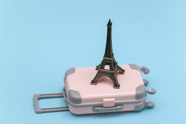 Nach paris gereist. mini reisekoffer aus kunststoff und statuette des eiffelturms auf blauem hintergrund.