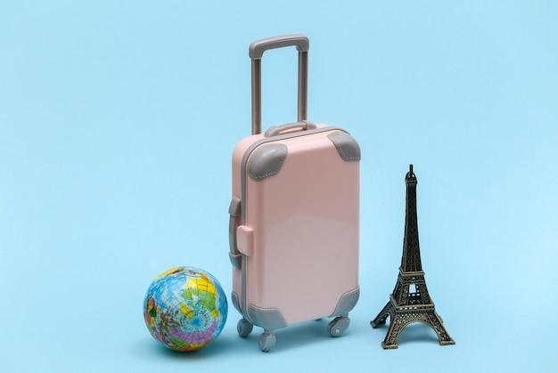 Nach paris gereist. mini reisekoffer aus kunststoff und statuette des eiffelturms, globus auf blauem hintergrund.