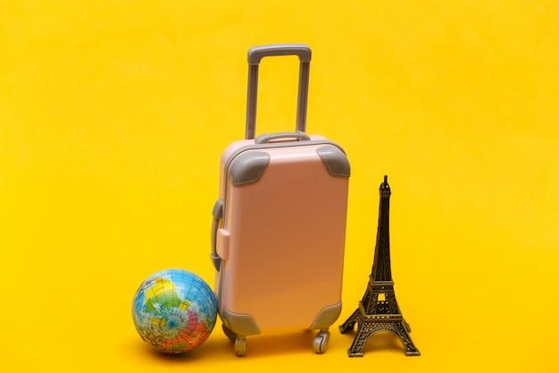 Nach paris gereist. mini reisekoffer aus kunststoff und statuette des eiffelturms, globus auf gelbem hintergrund.