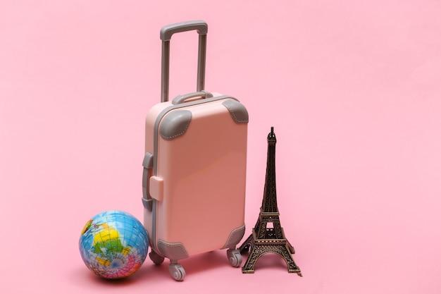 Nach paris gereist. mini reisekoffer aus kunststoff und statuette des eiffelturms, globus auf rosa hintergrund.