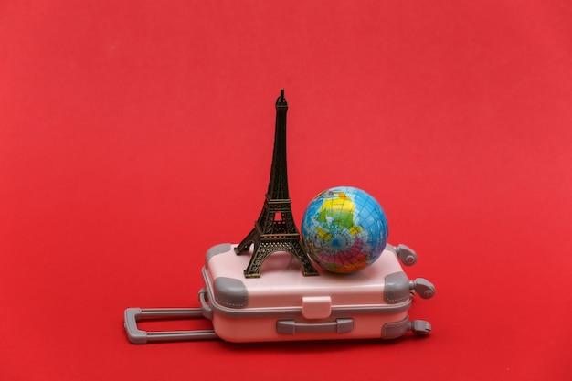 Nach paris gereist. mini reisekoffer aus kunststoff und statuette des eiffelturms, globus auf rotem grund.