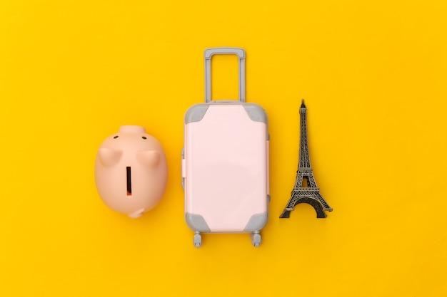 Nach paris gereist. mini-reisekoffer aus kunststoff und statuette des eiffelturms, sparschwein auf gelbem hintergrund. ansicht von oben. flach legen