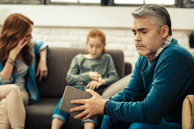 Nach psychologischer sitzung. netter ernster mann, der sein notizbuch schließt, während er eine psychologische sitzung mit seinen patienten hat