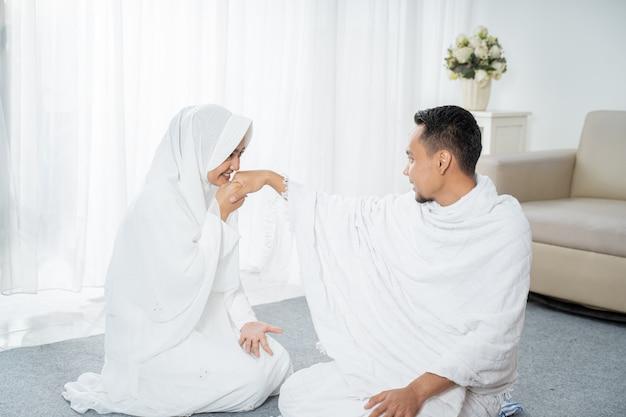 Nach sholat frau, die ehemanns hand küsst, die weiße traditionelle kleidung trägt