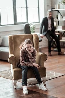 Nach streit. teenager, der im sessel sitzt und sich nach dem streit mit dem vater, der hinter ihr steht, schrecklich fühlt