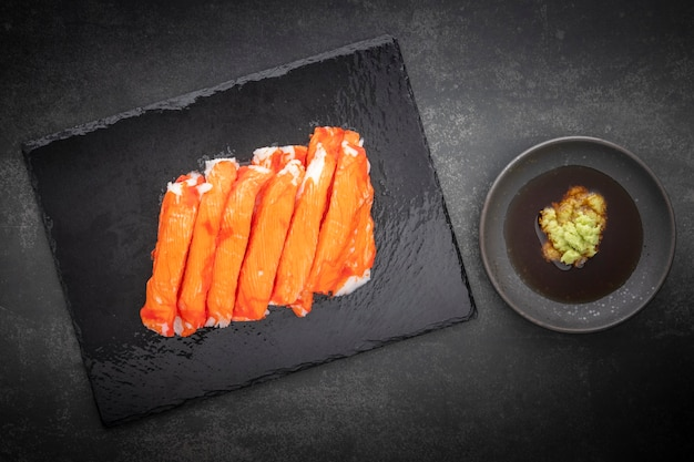 Nachahmung von alaska-krabbenstäbchen mit wasabi und shoyu-sojasauce in schwarzem schiefer auf dunklem texturhintergrund, ansicht von oben