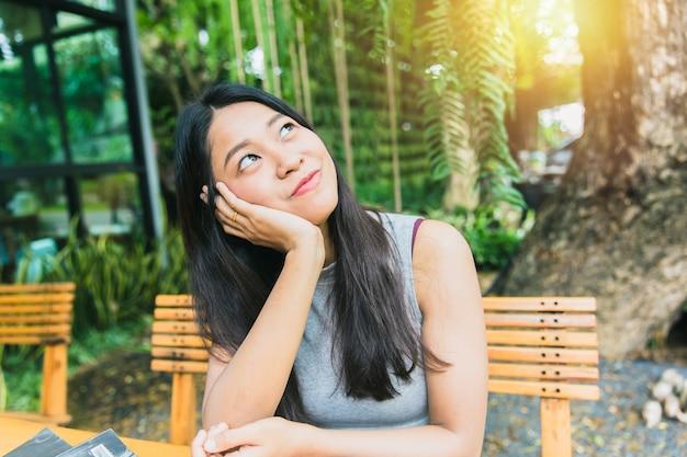 Nachdenken oder fehlendes passiertes gedächtnis. haar-kinnrest der thailändischen langen haarhand und die aufpassende vision der asiatischen frauen schauen weit weg mit sonnenlicht auf café