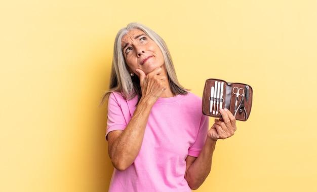 Nachdenken, sich zweifelnd und verwirrt fühlen, mit verschiedenen optionen, sich fragen, welche entscheidung man treffen soll, einen nagelwerkzeugkoffer zu halten