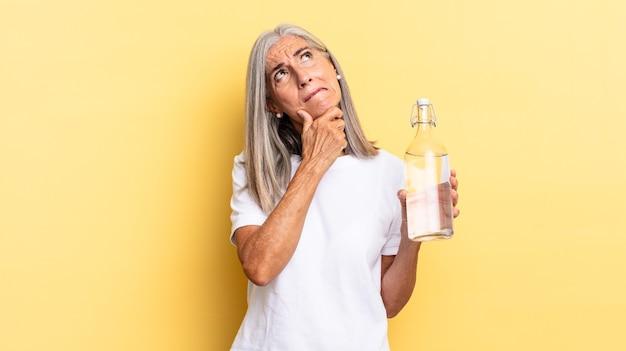 Nachdenken, sich zweifelnd und verwirrt fühlen, mit verschiedenen optionen, sich fragen, welche entscheidung man treffen soll und eine wasserflasche halten