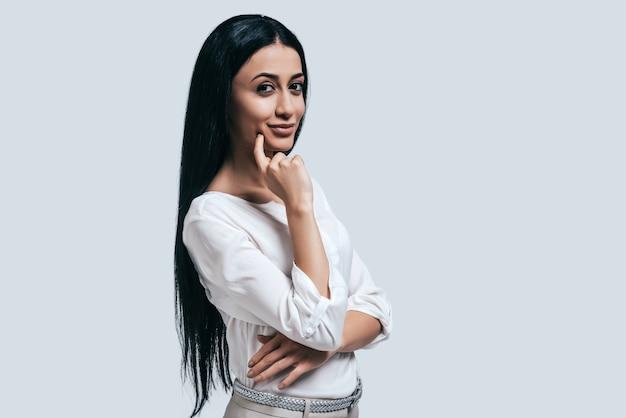Nachdenken über neue geschäftsansätze. selbstbewusste junge frau im weißen hemd, die lächelt und in die kamera schaut, während sie vor grauem hintergrund steht