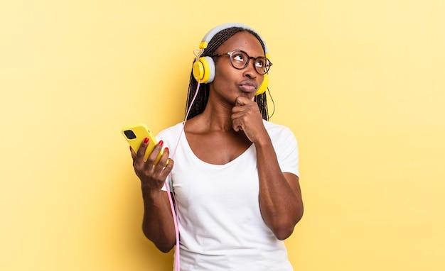 Nachdenken, zweifelnd und verwirrt fühlen, mit verschiedenen optionen, sich fragen, welche entscheidung man treffen soll und musik hören