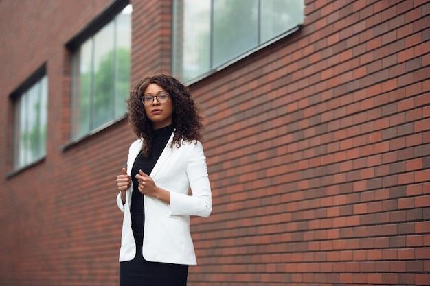 Nachdenklich. afroamerikanische geschäftsfrau in bürokleidung lächelnd, sieht selbstbewusst und ernst aus, beschäftigt. konzept für finanzen, wirtschaft, gleichstellung und menschenrechte. schönes junges modell, erfolgreich.