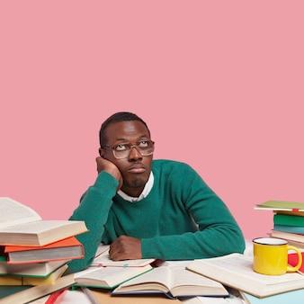 Nachdenklich gelangweilter schwarzer mann hält hand auf wange, schaut nach oben, trägt grünen pullover, optische brille, denkt über neue projektarbeit nach