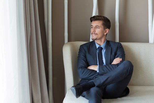Nachdenklich geschäftsmann sitzt in büro-vorhalle