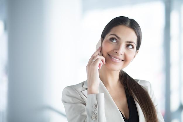 Nachdenklich hübsche geschäftsfrau, die am telefon spricht