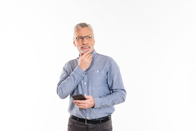 Nachdenklich lächelnder mann, der smartphone hält und isoliert denkt