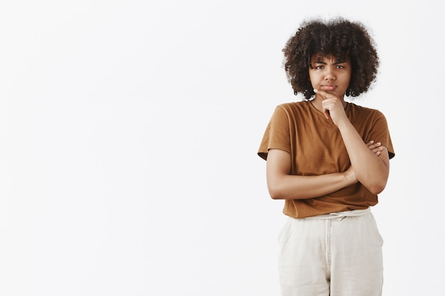 Nachdenklich misstrauisch und zweifelhaft niedlich afroamerikanische teenager-mädchen mit afro-frisur in braunem t-shirt händchenhalten auf kinn stirnrunzeln beim denken schauen mit unglauben und grinsen