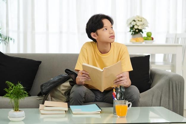 Nachdenklich oder gelangweilt, vietnamesischer teenager, der mit aufgeschlagenem buch auf dem sofa sitzt und nach oben schaut