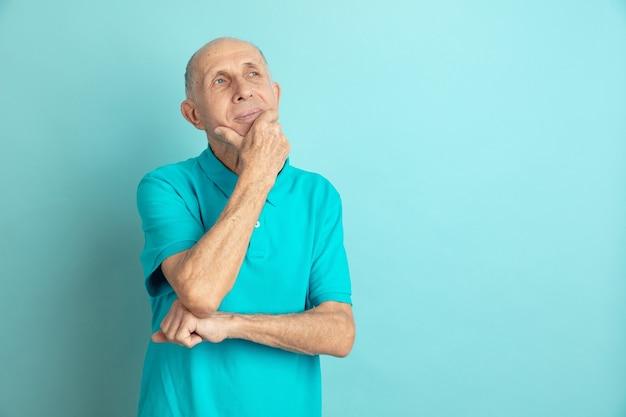 Nachdenklich, träumend. porträt des kaukasischen älteren mannes lokalisiert auf blauem studiohintergrund. schönes männliches emotionales modell. konzept der menschlichen emotionen, gesichtsausdruck, verkauf, wohlbefinden, anzeige. copyspace.