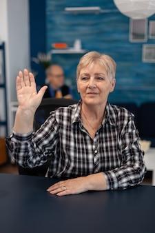 Nachdenkliche ältere dame, die die leute während der online-konferenz begrüßt greeting