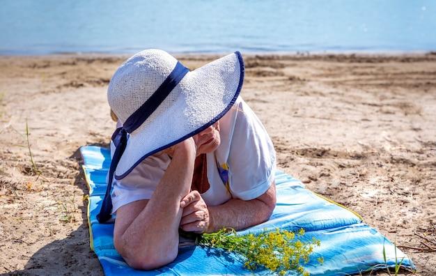 Nachdenkliche ältere frau, ältere rentnerin, ruhen auf dem sand am fluss