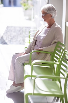 Nachdenkliche ältere frau, die auf stuhl sitzt