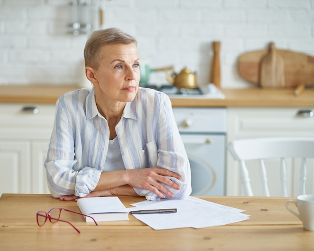 Nachdenkliche ältere frau, die über etwas nachdenkt, während sie in der küche sitzt und mit arbeitet