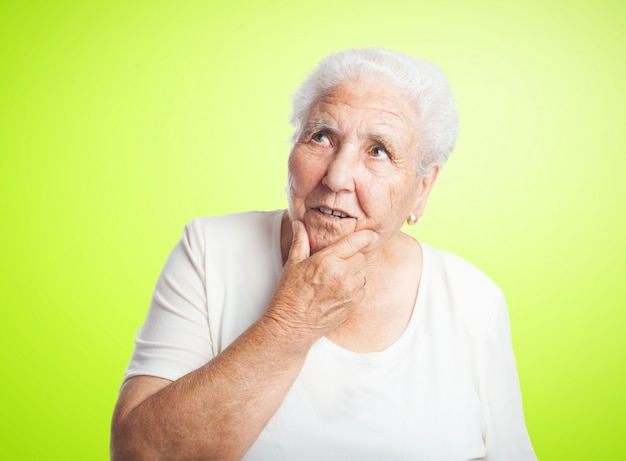 Nachdenkliche ältere frau mit einer hand am kinn