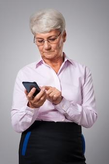 Nachdenkliche ältere geschäftsfrau, die smartphone benutzt