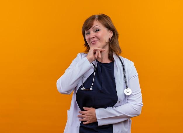 Nachdenkliche ärztin mittleren alters, die medizinische robe und stethoskop trägt und hände auf kinn und bauch auf isolierte orange wand mit kopienraum setzt