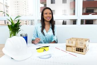 Nachdenkliche Afroamerikanerdame auf Stuhl nahe Schutzhelm und Modell des Hauses auf Tabelle