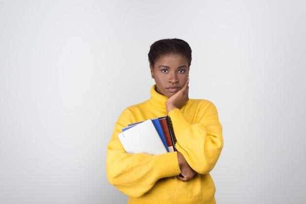 Nachdenkliche afroamerikanerin, die bücher hält