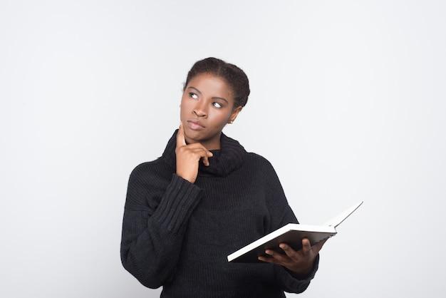 Nachdenkliche afroamerikanerin, die offenes notizbuch hält