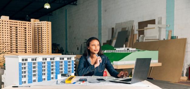 Nachdenkliche afroamerikanische dame mit laptop und modell des gebäudes