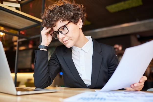 Nachdenkliche analytikerin berührt ihre stirn, während sie versucht, sich auf das lesen von online-informationen zu konzentrieren