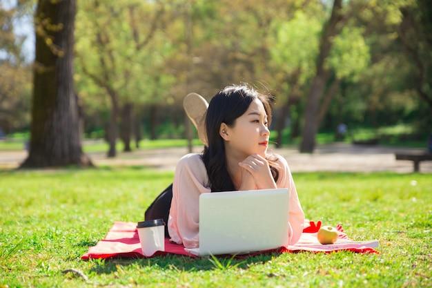 Nachdenkliche asiatin, die an laptop-computer auf rasen arbeitet